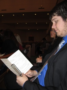 Joseph watching the play by play on his phone inside of the wedding program